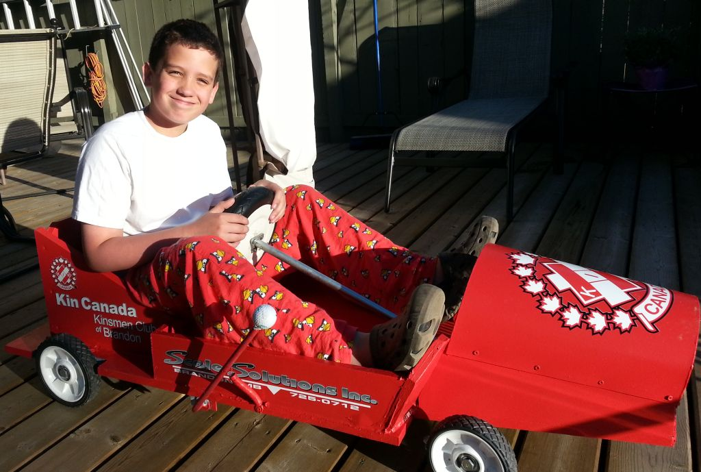 Adam Wiebe, trying out the Kinsmen Club of Brandon Soap Box Derby car.