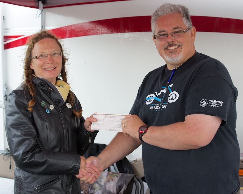 Brenda Hales (L) winner of the  the $500 poker derby, accepts the prize from Art Wiebe (R) President of the Kinsmen Club of Brandon