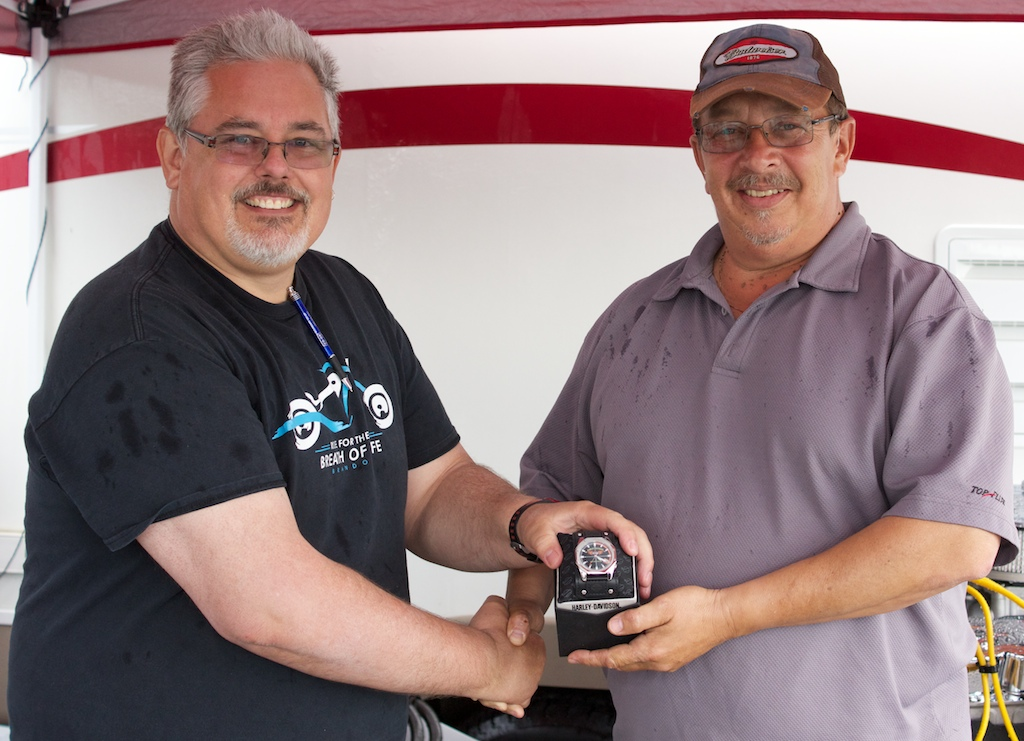 Rick Reimer (R) accepts the raffle prize of a Harley Davidson watch from Art Wiebe (L) President of the Kinsmen Club of Brandon