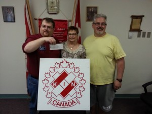 James Sewell and Art Wiebe of the Kinsmen Club of Brandon accepting the cheque from Rose Hercun of the Brandon Scrapbookers